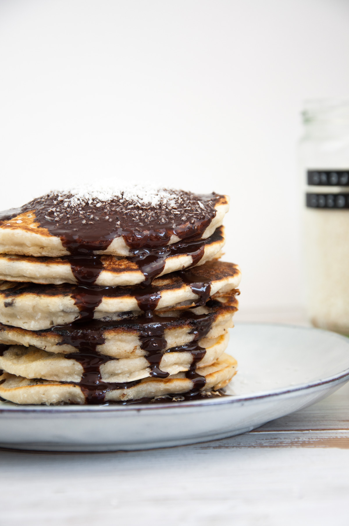 Vegan Coconut Pancakes topped with chocolate sauce and coconut flakes